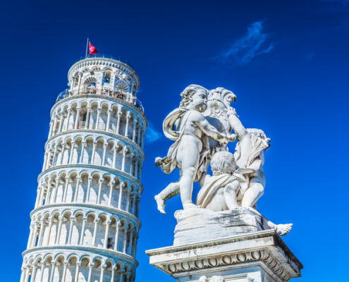 Famous leaning tower in Pisa Italy with statue of angels in foreground.